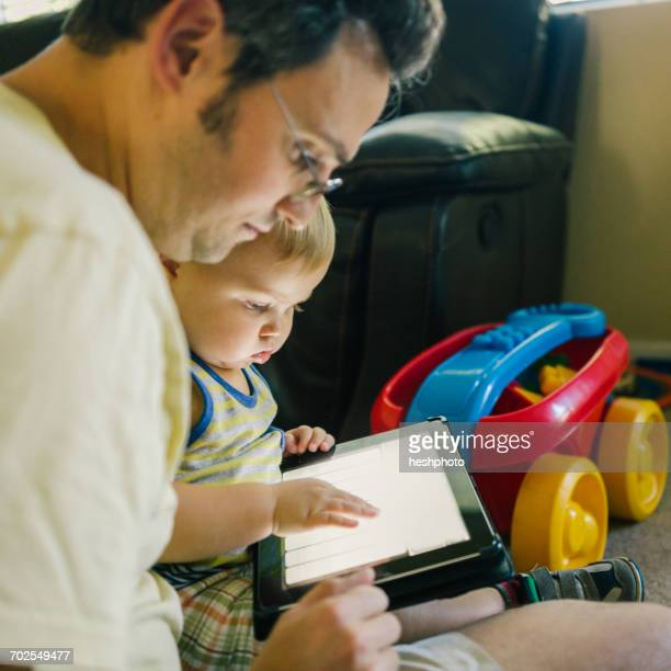 father and young son looking at digital tablet - heshphoto imagens e fotografias de stock