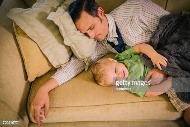 father and young son lying on sofa together - heshphoto stockfoto's en -beelden