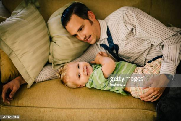 father and young son lying on sofa together - heshphoto stock pictures, royalty-free photos & images