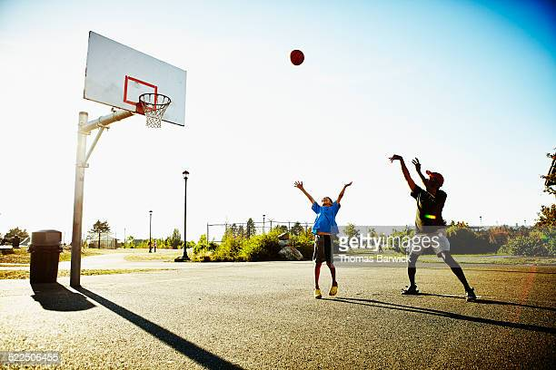 Father and young son playing basketball in park