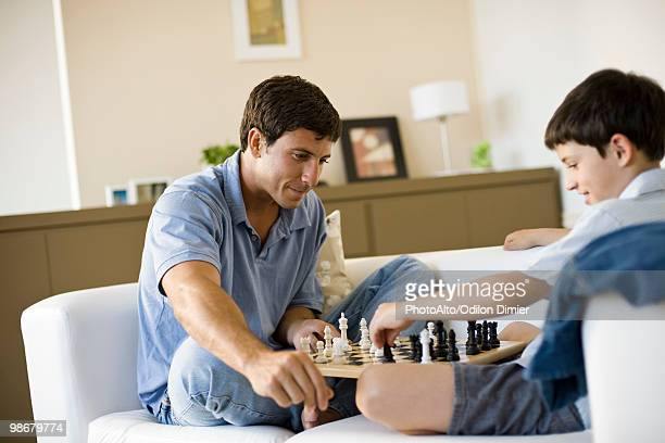 Father and young son playing chess