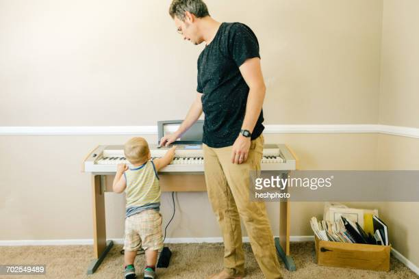 father and young son playing musical keyboard together - heshphoto stock pictures, royalty-free photos & images