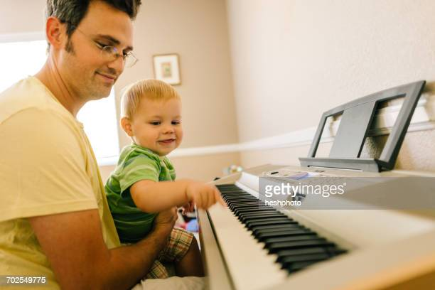 father and young son playing musical keyboard together - heshphoto fotografías e imágenes de stock