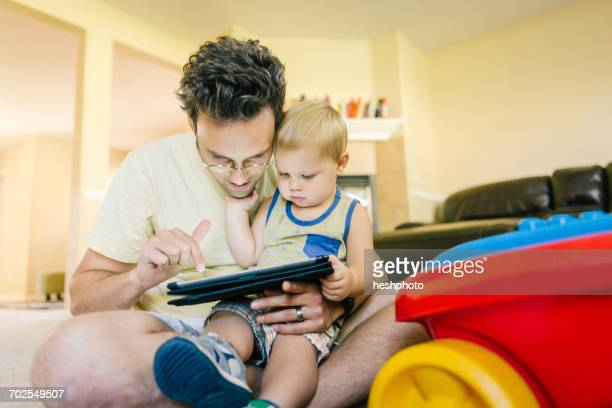 father and young son playing together at home, looking at digital tablet - heshphoto fotografías e imágenes de stock