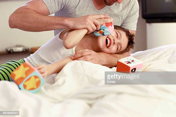 Father and young son playing with building blocks on bed
