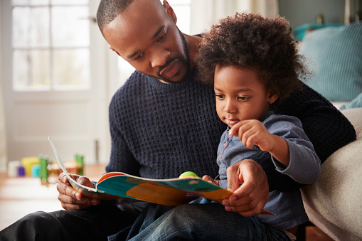 Father And Young Son Reading Book Together At Home 961758544