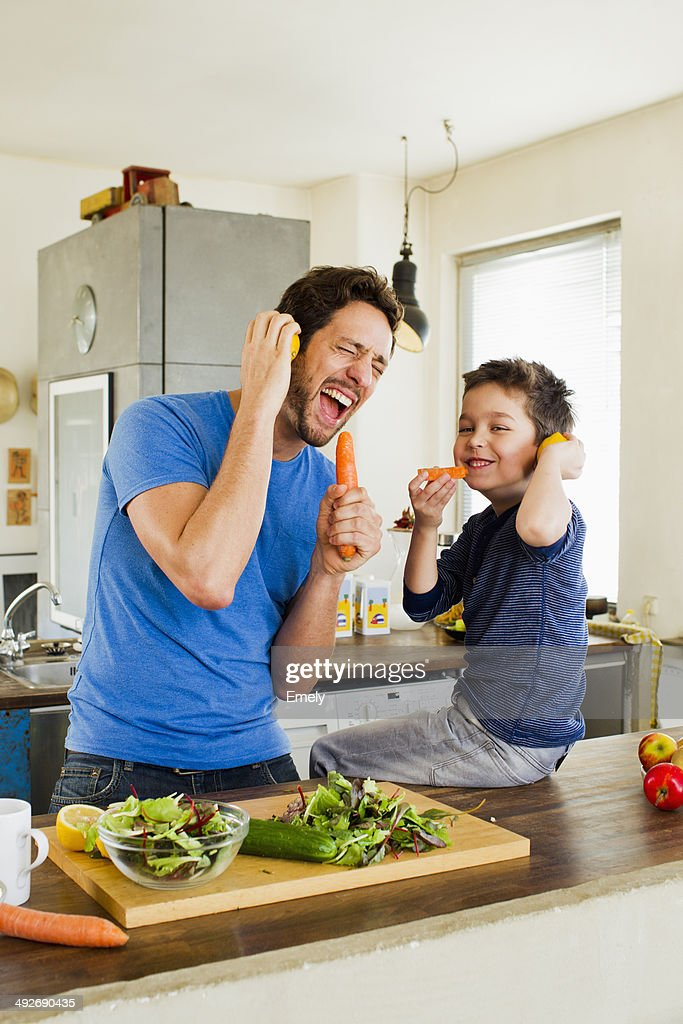 Father and young son singing into carrot microphones : Stock Photo