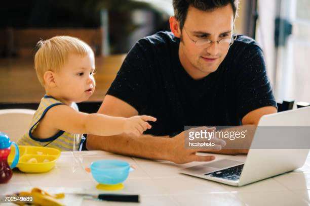 father and young son sitting at table, father using laptop, son pointing at screen - heshphoto fotografías e imágenes de stock