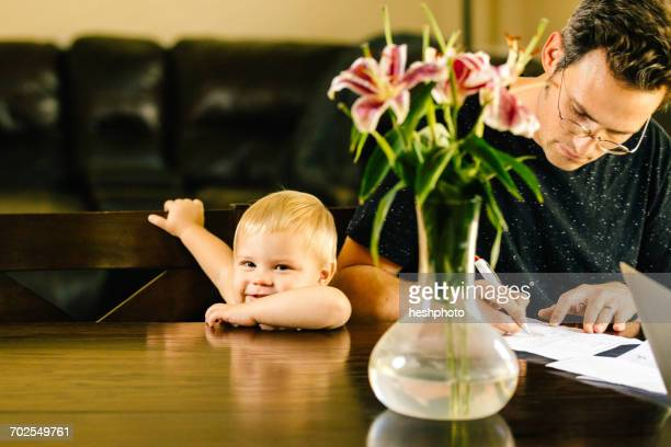 father and young son sitting at table, father writing on document - heshphoto stock pictures, royalty-free photos & images