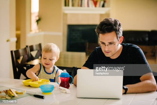 father and young son sitting at table, son eating, father using laptop - heshphoto stockfoto's en -beelden
