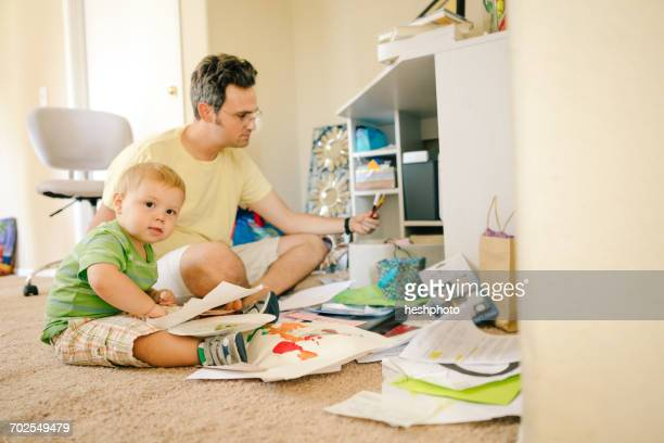 father and young son sitting on floor creating artwork - heshphoto stock-fotos und bilder