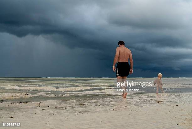 Father and Young Son walk on the Beach with Storm in Background
