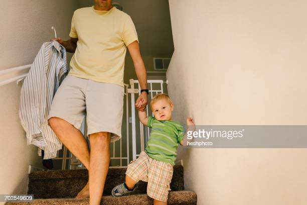 father and young son walking downstairs, holding hands, father holding shirt on hanger - heshphoto stockfoto's en -beelden