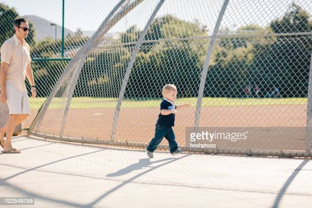 father and young son walking in playground - heshphoto stock pictures, royalty-free photos & images