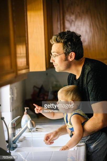 father and young son washing hands at sink, looking out of window - heshphoto bildbanksfoton och bilder