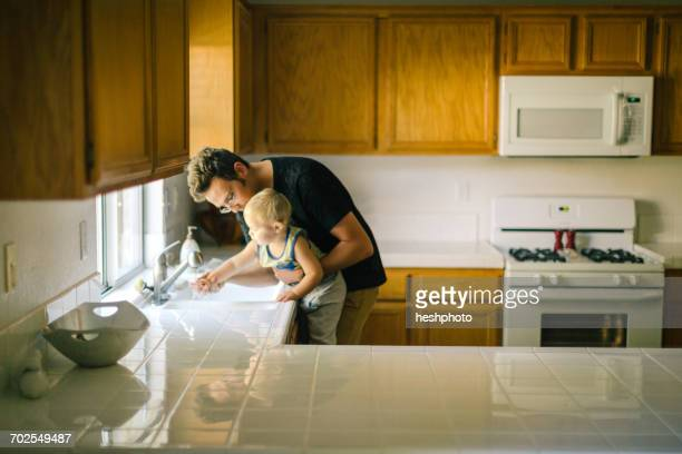 father and young son washing hands at sink - heshphoto stock pictures, royalty-free photos & images