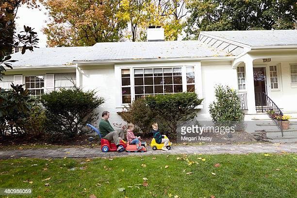 Father and young sons riding on toy cars in garden