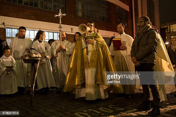 Father Andrea Fulco speaks to parishioners during Easter Vigil service outside St Peter's Italian Church in Farringdon on March 26 2016 in London...