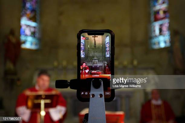 Father Andrew James and Bishop Richard Umbers are seen livestreaming 'The Celebration of the Passion of The Lord' service at St Paul of the Cross...