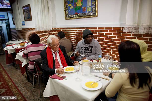 Father Angel sits on a table to share dinner with homeless people as he shows the place to the press at Robin Hood restaurant on December 5 2016 in...