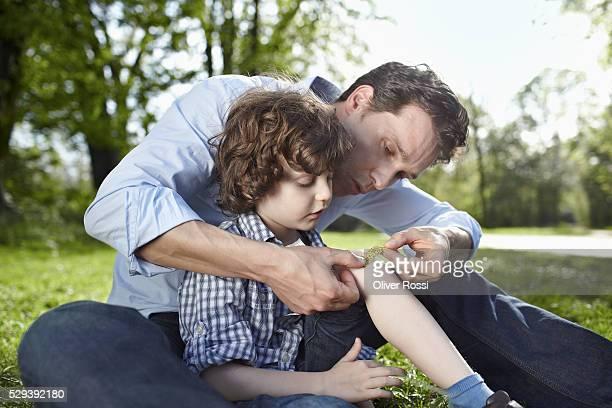 father applying bandaid to son's (7-9) knee in park - esparadrapo fotografías e imágenes de stock