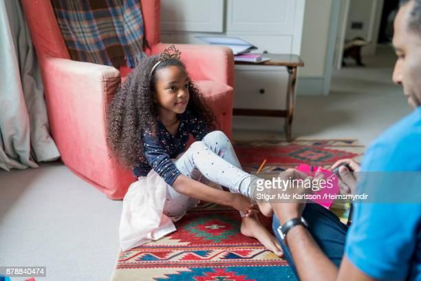Father applying nail polish on daughter's toenail