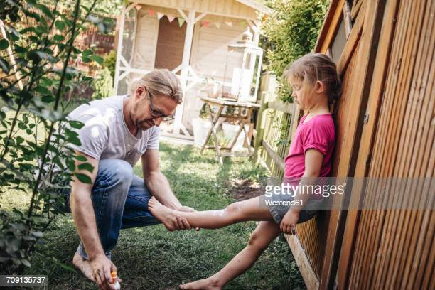 Father applying sunscreen on daughters legs in garden