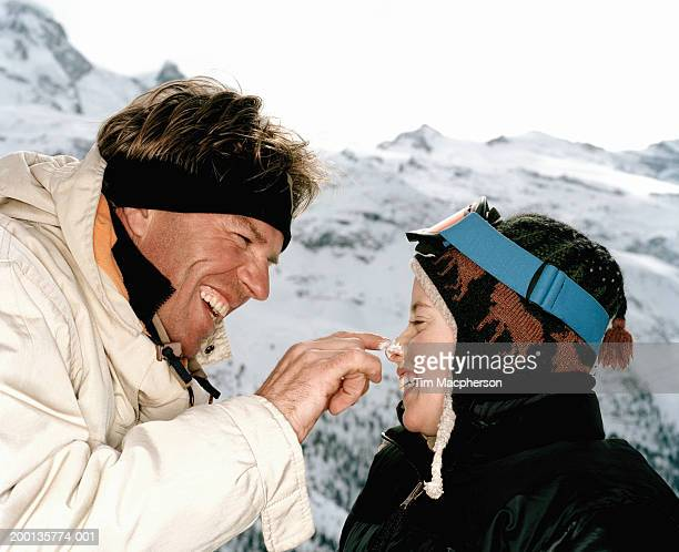 Father applying sunscreen to son's nose, in snow, close-up