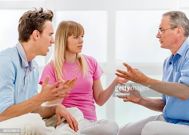 Père expliquant avec ses enfants à la maison.