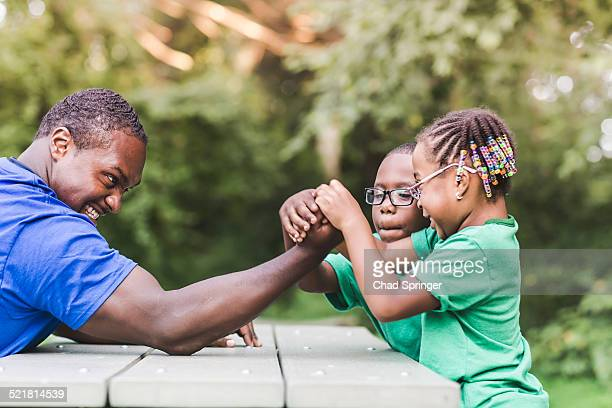 Father arm wrestling with daughter at parkland eco camp