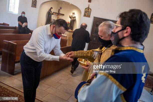 Father Armenag Bedrossian hands out wafers to parishioners during communion at Our Lady Queen of Martyrs Church, an Armenian church on Sunday, April...