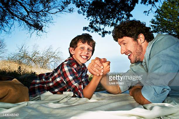 Father arm-wrestling with son (6-8) at picnic