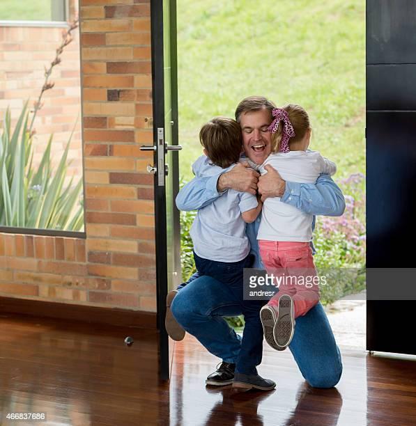 Père embrassant son arrivée à la maison et pour les enfants