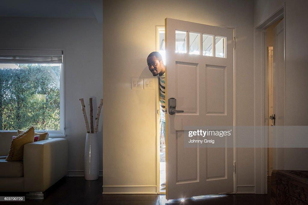 Father Arriving Home Peeping Through Open Front Door Stock Photo