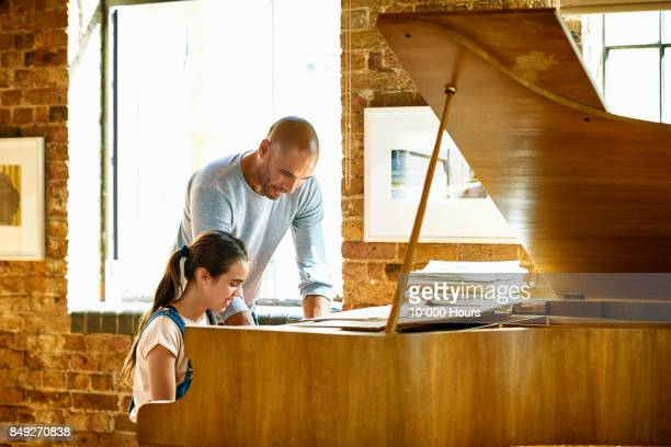 Father assisting daughter playing grand piano