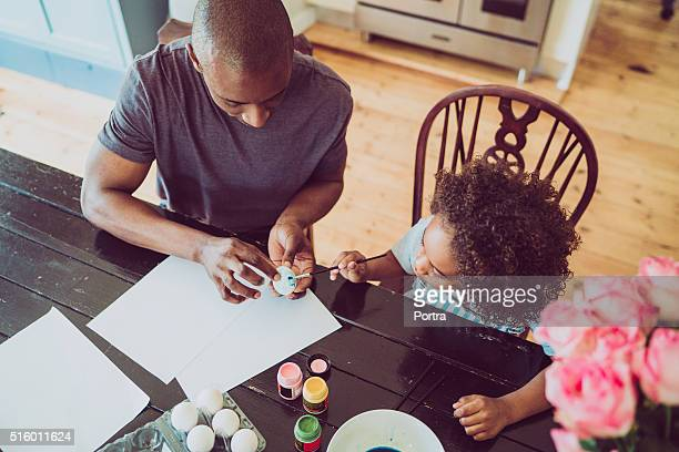 Father assisting girl in painting Easter egg at home