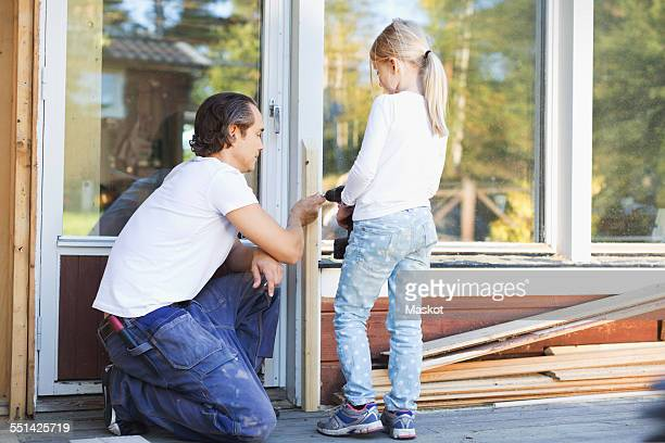 Father assisting girl in using cordless screwdriver on frame during home improvement