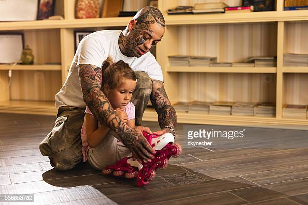Father assisting his daughter with roller skates at home.