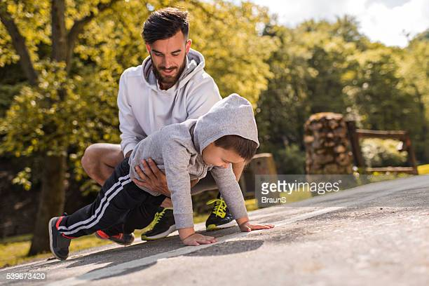 Father assisting little boy in doing push-ups in the park.