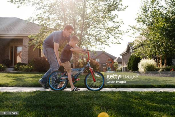 father assisting son in riding bicycle on road against sky - 乗る ストックフォトと画像