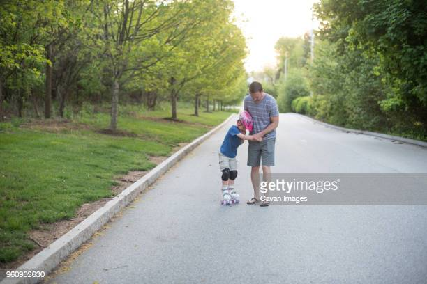 Father assisting son in roller skating on road at park