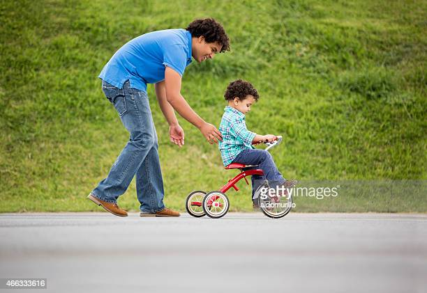 Father assisting son in tricycle