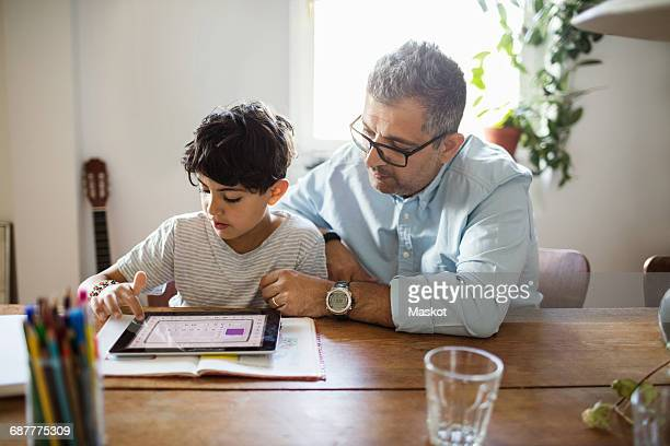 father assisting son in using digital tablet at home - één ouder stockfoto's en -beelden