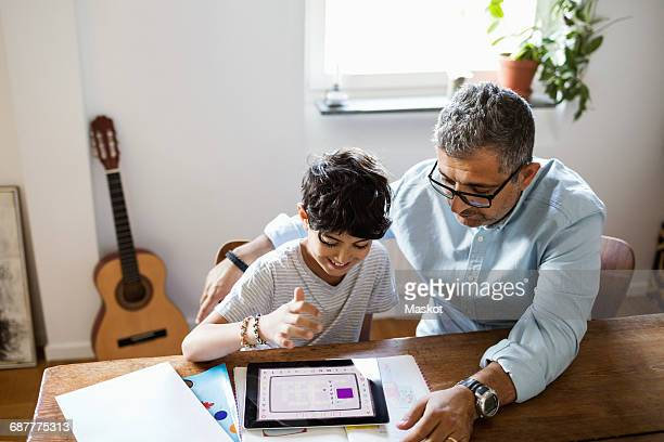Father assisting son in using digital tablet while studying at home
