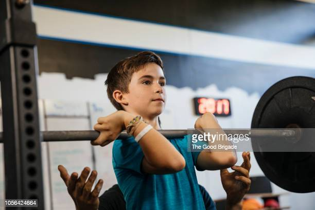 father assisting son lifting weights in gym - kids weightlifting ストックフォトと画像