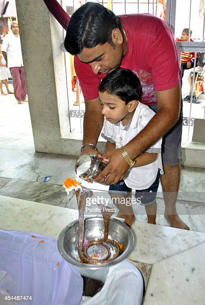 Father assists his son to offer milk and prayers to a snake during the annual Hindu Nag Panchami festival in Jammu