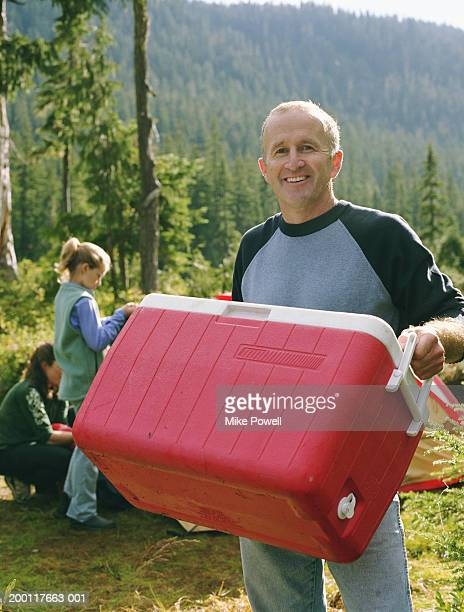 father at camping site with family, carrying cooler, portrait - esky stock photos and pictures