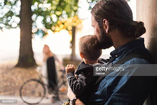 Father at door holding baby boy while looking at woman leaving for work