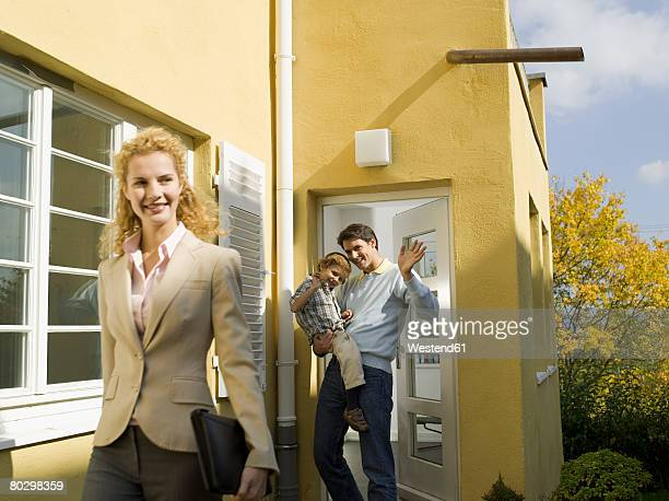 Father at door holding son (3-4), mother leaving for work, smiling