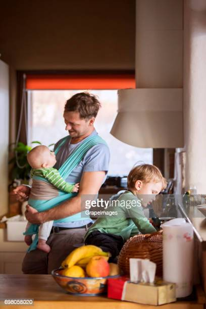 Father at home in the kitchen, baby son in the sling, older son sitting on kitchen countertop